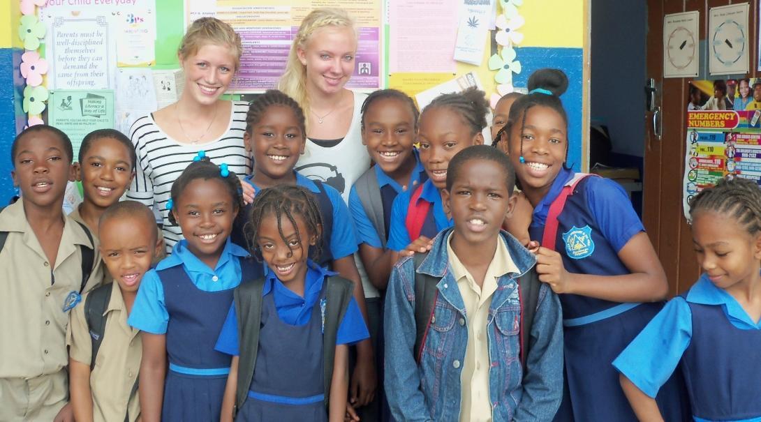 Voluntarios de educación en Jamaica posan junto a sus estudiantes.